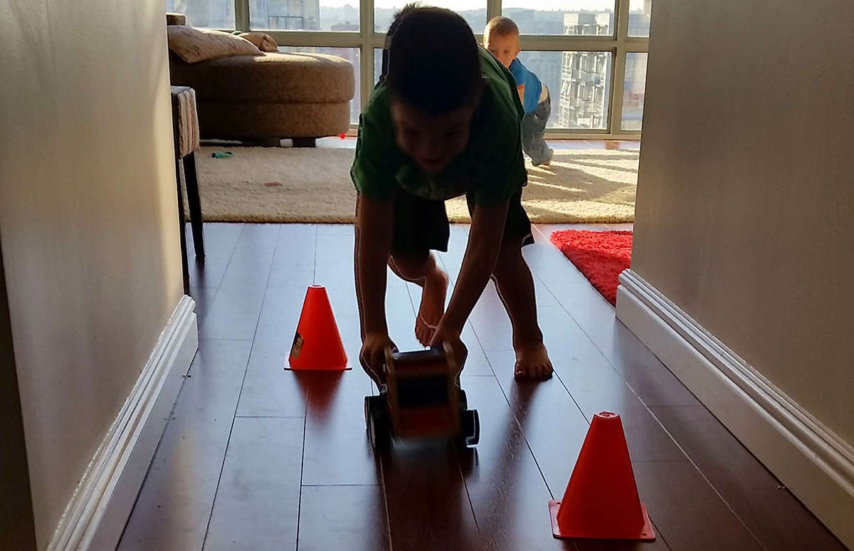 The middle nerd sets up pylons to race his push car around.
