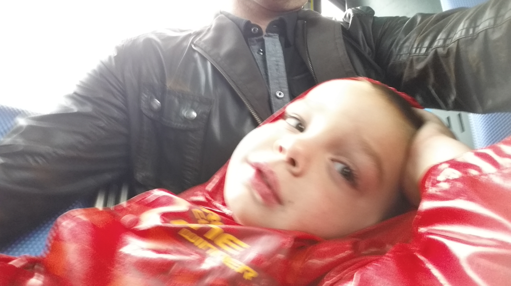 My youngest lounges on my lap during a bus ride.