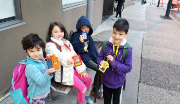 The kids proudly display their Compass cards (transit passes) on our first official day of car-free living.