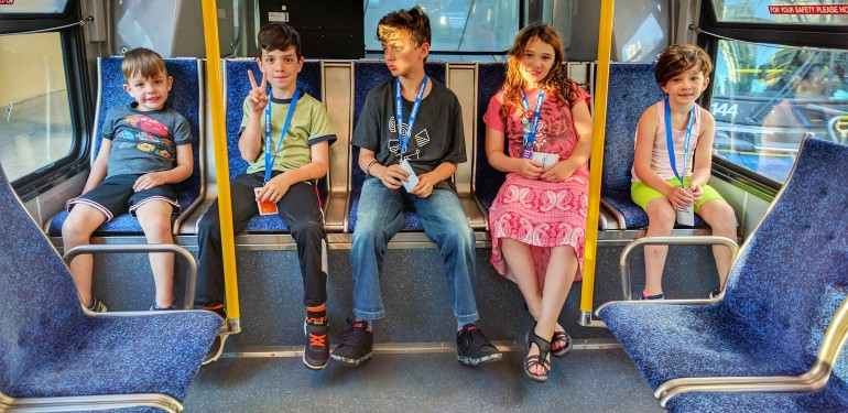 The kids (including the littlest one), chilling at the back of the bus, on our way to English Bay.